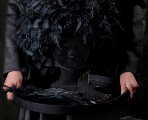 Black coat withblack feather headpiece charcoal symbolism - Fashion still life Ruud van Ooij