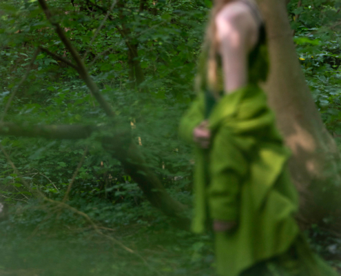 Out of focus green dress with green coat in forest - Fashion photography Ruud van Ooij